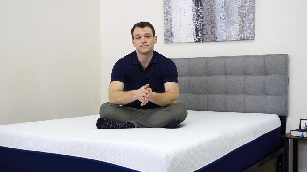Amerisleep-Comparison-Sitting-On-Bed Best Memory Foam Mattress